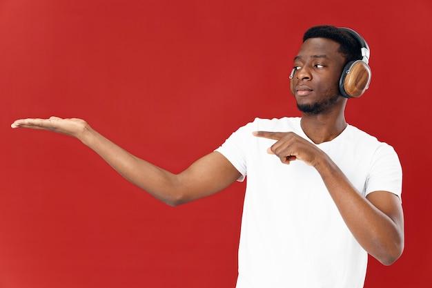 ハンドコピースペースで身振りで示すヘッドフォンと白いtシャツのアフリカ系アメリカ人。高品質の写真
