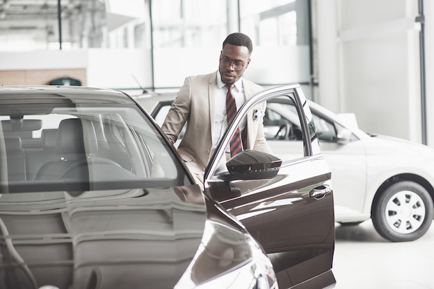 An african american inspects the car at the car dealership. good bargain.