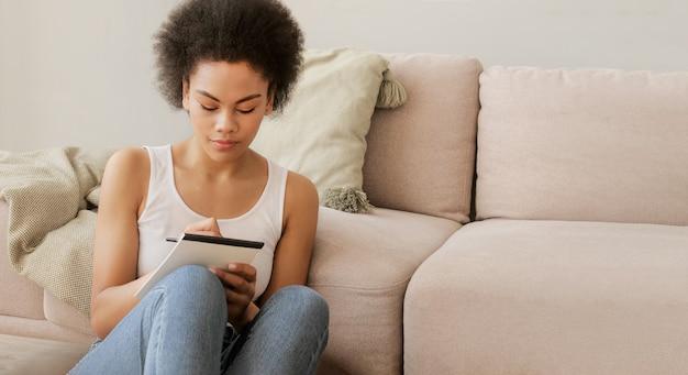 아프리카계 미국인 영감을 받은 여성은 종이 일기장에 생각에 잠겨 생각하고 메모를 작성합니다.