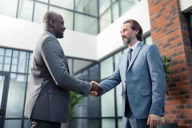 아프리카계 미국인 투자자. 그의 아프리카계 미국인 투자자를 만나면서 웃고 있는 수염난 사업가