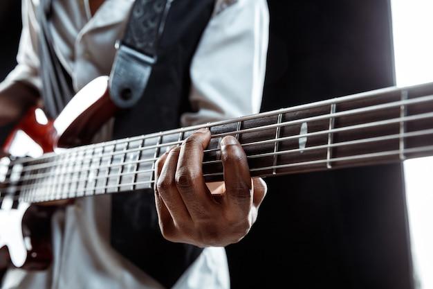 African american jazz musician playing bass guitar.