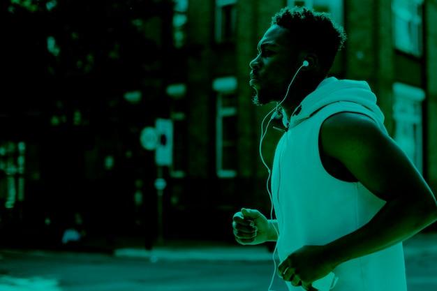 Afroamericano che fa jogging ascoltando musica