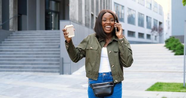 アフリカ系アメリカ人のうれしそうな若いスタイリッシュな女性が携帯電話で話し、温かい飲み物を飲みながら、朝通りを歩いています。携帯電話で話し、コーヒーを飲む美しい幸せな女性。外側。