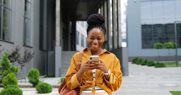 スマートフォンをタップまたはスクロールし、街の通りに立っているアフリカ系アメリカ人の楽しい若いスタイリッシュな女性。携帯電話と笑顔で美しい幸せな女性のテキストメッセージ。外側。