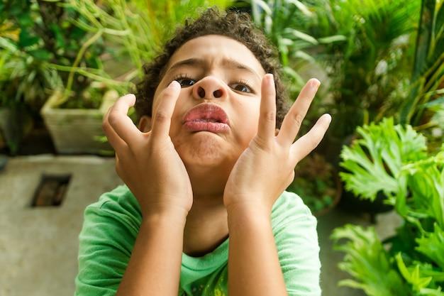 Афро-американский ребенок корчит рожи и веселится в саду