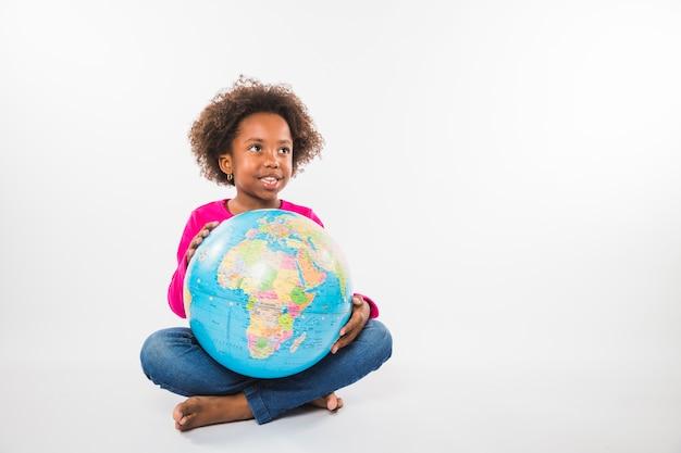 スタジオで地球儀を持つアフリカ系アメリカ人の子供