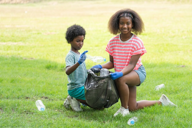 Афроамериканские дети добровольно собирают пластиковые бутылки в черный мешок для мусора в парке, помогите собрать мусор в благотворительной среде
