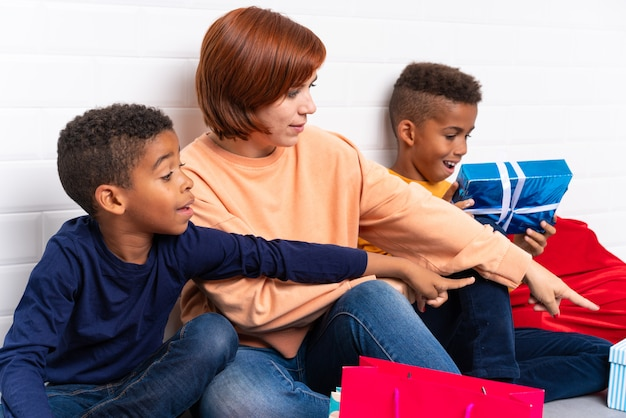 African american kids with their mother among many gifts for christmas holidays