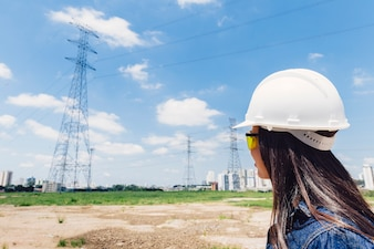 African American lady in safety helmet near high voltage line