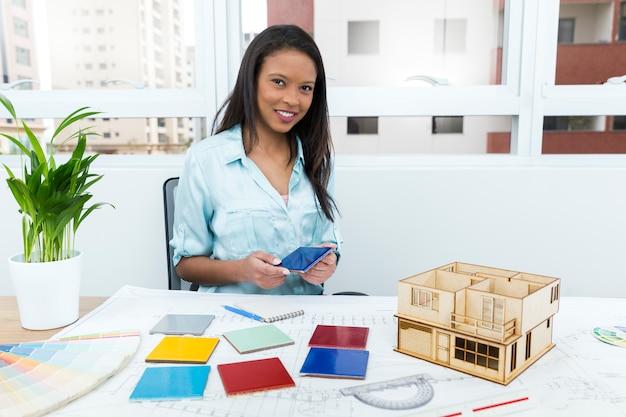 Афроамериканская леди на стуле с фасадной панелью около плана и модели дома на столе
