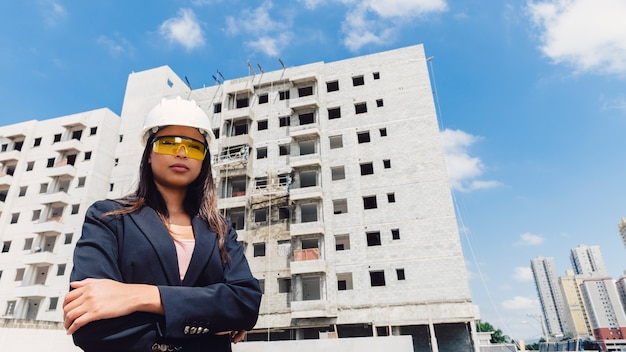 African american lady in safety helmet and eyeglasses near building under construction