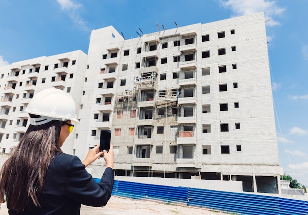 African american lady in safety helmet taking photo of building under construction