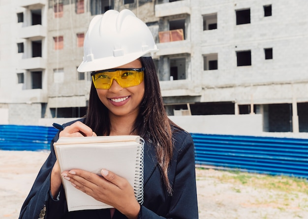 African american lady in safety helmet writing in notebook near building under construction