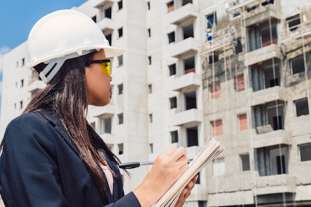 African american lady in safety helmet writing in notepad near building under construction