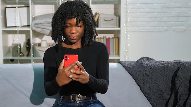 スマートフォンで巻き毛のタイプのアフリカ系アメリカ人の女性
