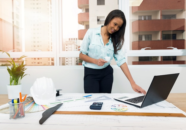 African-american lady with paper near laptop and plan on table with equipments