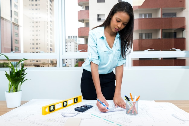 Афро-американская леди с ручкой и линейкой возле плана на столе с оборудованием