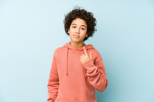 Афро-американский маленький мальчик изолировал указывая пальцем на вас, как будто приглашая подойти ближе.