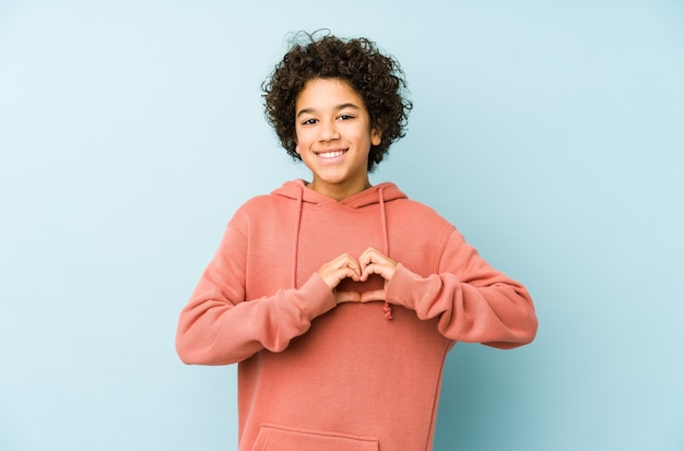 African american little boy isolated smiling and showing a heart shape with hands.