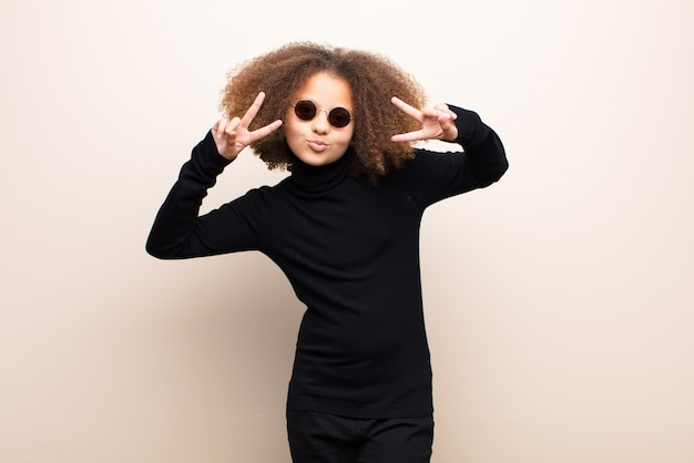 African american little girl  against flat wall. cool concept