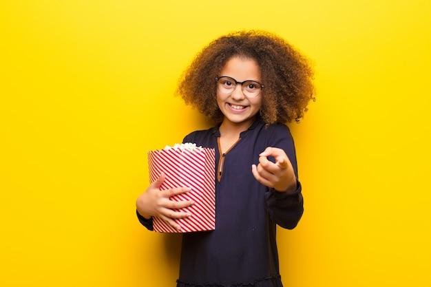 Афро-американская маленькая девочка против плоской стены, держащей ведро попкорна