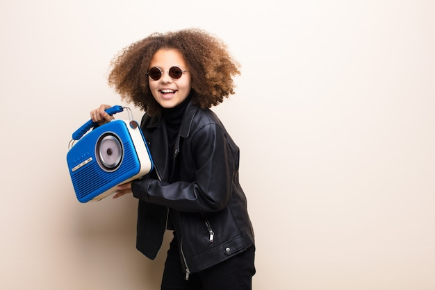 African american little girl against flat wall listening music with a oldfashioned radio