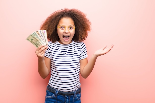 African american little girl  against flat wall with dollar banknotes