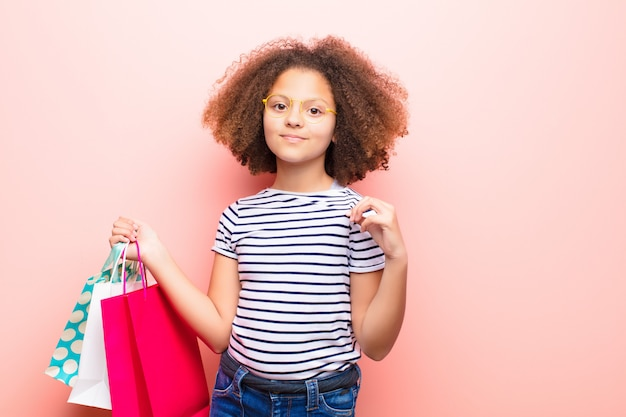 Афро-американская маленькая девочка против плоской стены с хозяйственными сумками
