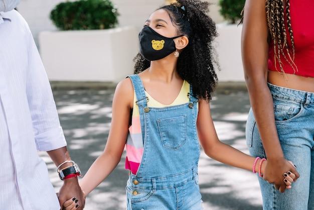 그녀의 부모와 함께 길을 걷고있는 동안 야외에서 하루를 즐기는 아프리카 계 미국인 소녀. 새로운 정상적인 라이프 스타일 개념.