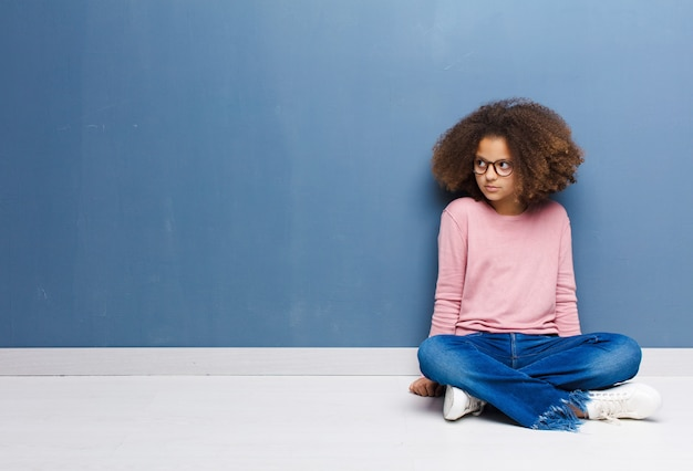 African american little girl feeling sad, upset or angry and looking to the side with a negative attitude, frowning in disagreement sitting on the floor