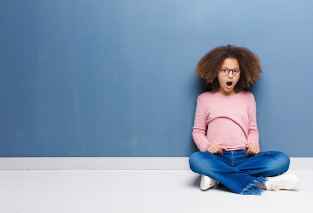 African american little girl looking shocked sitting on the floor