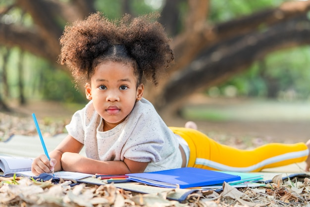 African american little girl lying drawing in a book at the park