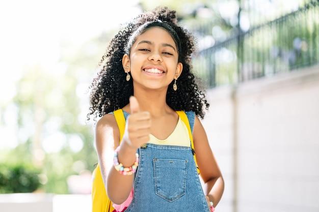 通りでバックパックを身に着けている間笑顔で親指を立ててアフリカ系アメリカ人の少女