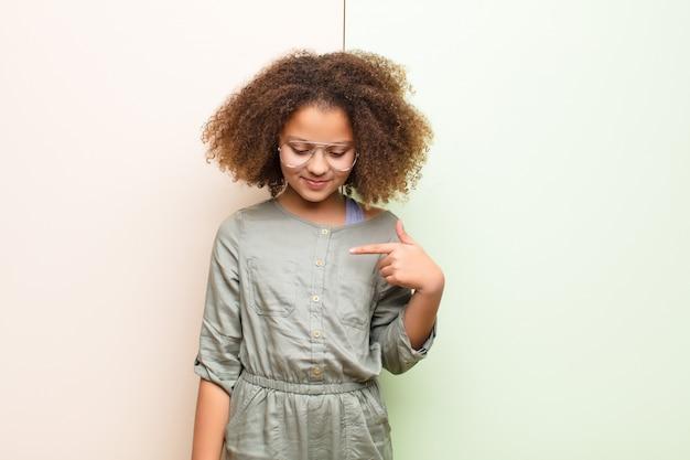 アフリカ系アメリカ人の少女が元気でさりげなく笑って、下向きに見て、胸を指して