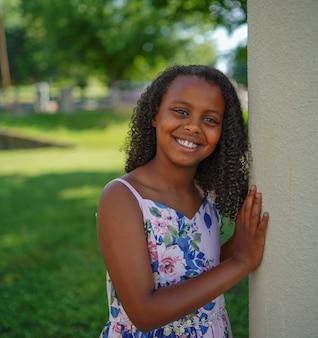 Афро-американская маленькая девочка улыбается в саду в окружении зелени под солнечным светом