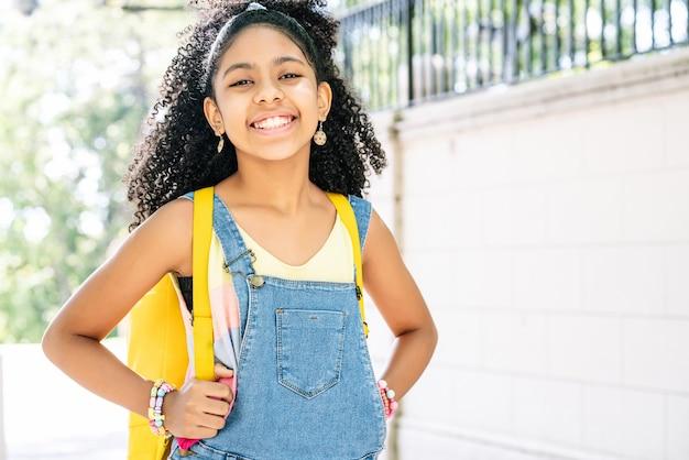 通りに立って笑っているアフリカ系アメリカ人の少女。教育の概念。