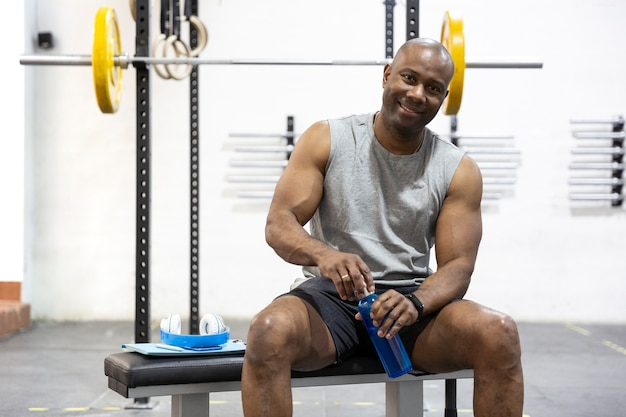 African american male athlete resting after sport in the gym. space for text.