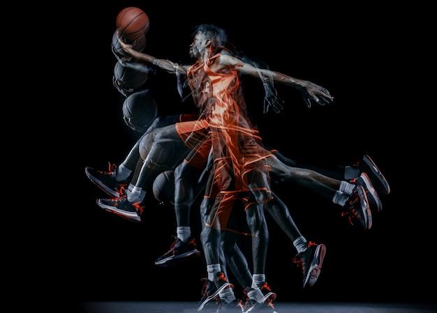 어두운 배경에서 격리된 동작과 행동을 하는 아프리카계 미국인 남성 농구 선수.