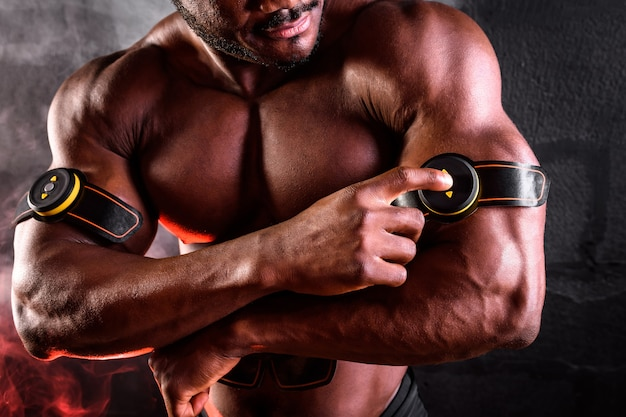 African american male bodybuilder uses electronic myostimulator to train biceps hands on a black background