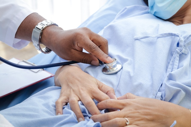 Афро-американский врач-мужчина проверьте болезнь женщины, лежащей на больничной койке. лечение больных во время эпидемии коронавируса. понятие о медицинском обслуживании.