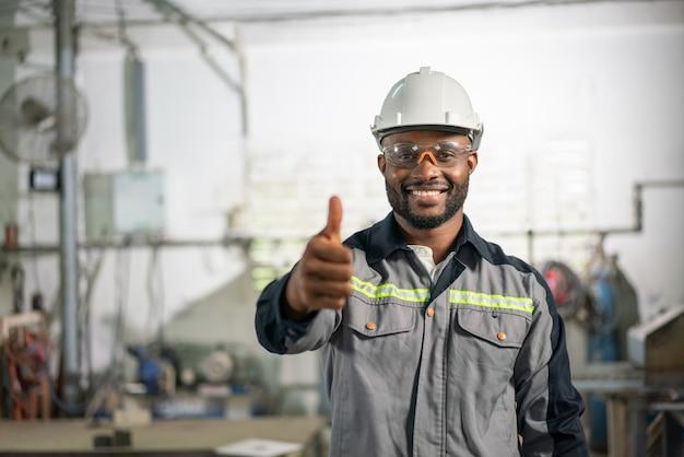 制服を着たアフリカ系アメリカ人の男性エンジニアが笑顔で、産業のfaで親指を表示