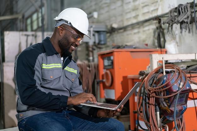 産業工場でコンピューターラップトップ制御ロボットアーム溶接機を使用しているアフリカ系アメリカ人の男性エンジニア。