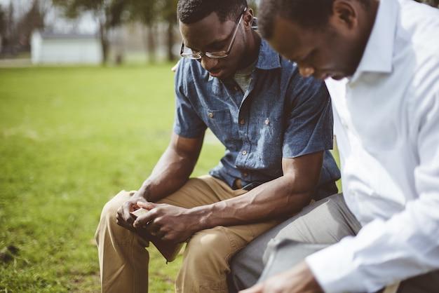 Amici maschi afroamericani seduti e pregando con gli occhi chiusi e la bibbia in mano