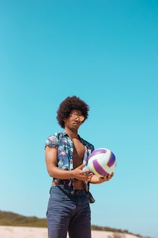 African american male holding ball on beach