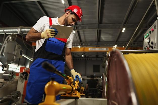 Афро-американский мужчина-менеджер на складе электрического кабеля с цифровым планшетом