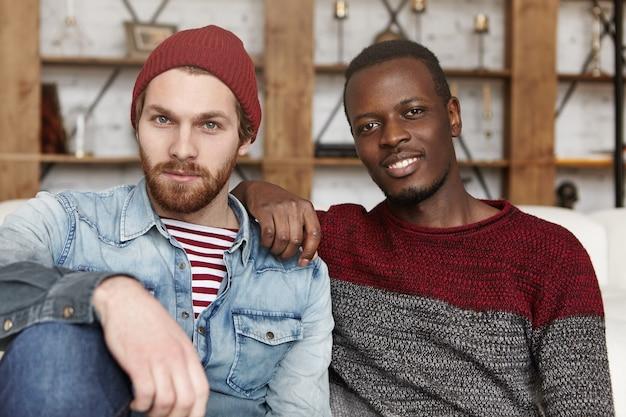 Афро-американский мужчина, опираясь локтем на плечо своего стильного друга