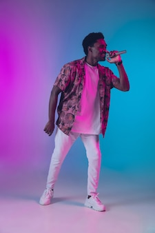 Афро-американский певец портрет изолирован на градиентном студийном фоне в неоновом свете