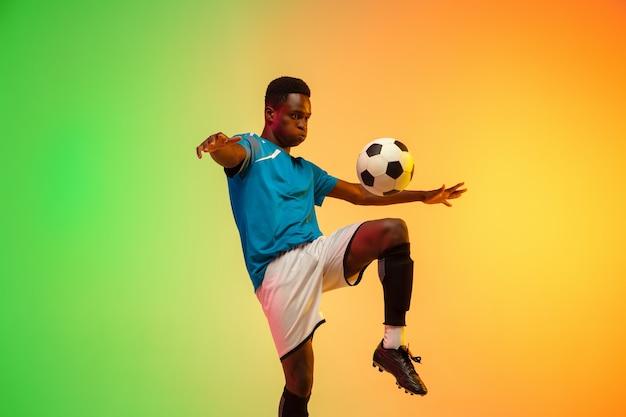 Афро-американский мужской футбол, обучение футболиста в действии, изолированные на фоне градиентной студии в неоновом свете. понятие движения, действия, достижений, здорового образа жизни. молодежная культура.