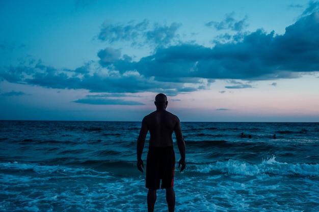 Афро-американский мужчина, стоящий у моря под голубым облачным небом, выстрелил сзади