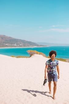 해변에서 맨발로 걷는 아프리카 계 미국인 남성